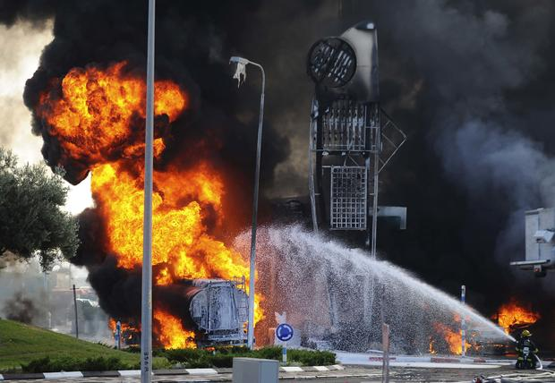 Israeli firefighters extinguish a fire that broke out after a rocket hit a petrol station in the southern Israeli city of Ashdod