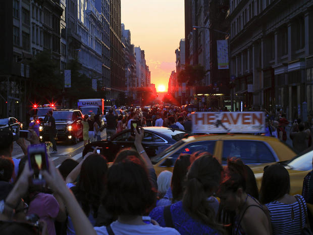People take pictures at sunset during the bi-annual occurrence of Manhattanhenge in New York July 11, 2014.