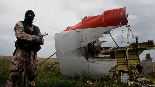 A pro-Russian rebel fighter stands next to a large piece of wreckage from Malaysia Airlines Flight 17
