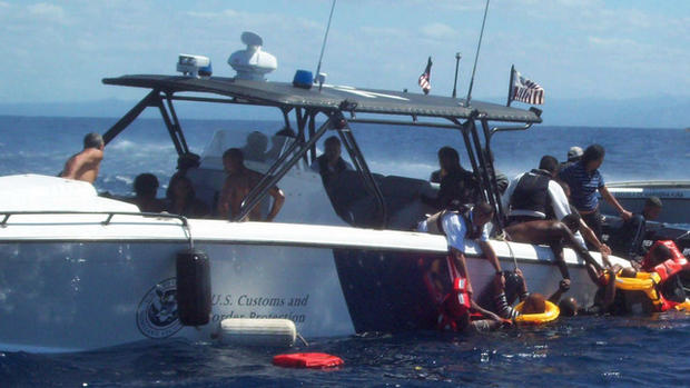 Office of Air & Marine agents pull migrants aboard their boat.