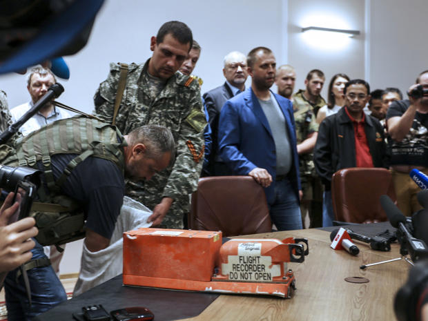 A pro-Russia separatist shows members of the media a black box belonging to Malaysia Airlines Flight 17 before handing it over to Malaysian representatives during a press conference in Donetsk, Ukraine, July 22, 2014.