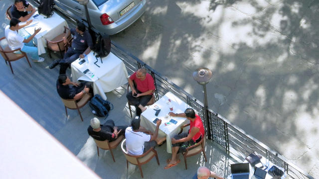 International inspectors sit outside at a hotel in Kharkiv, Ukraine, waiting for marching orders to try and reach the Malaysia Airlines Flight 17 crash site