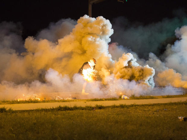 A protester throws back a smoke bomb while clashing with police in Ferguson, Missouri, Aug. 13, 2014.