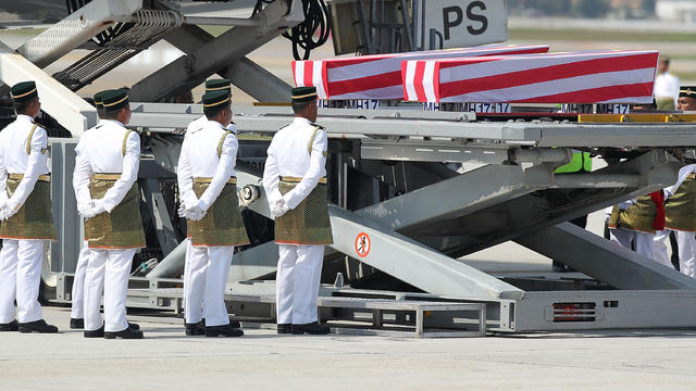 A plane carrying the bodies of 20 Malaysians killed in the downing of Malaysia Airlines Flight MH17 over Ukraine arrives and the coffins are prepared to be carried by Army soldiers at Kuala Lumpur International Airport