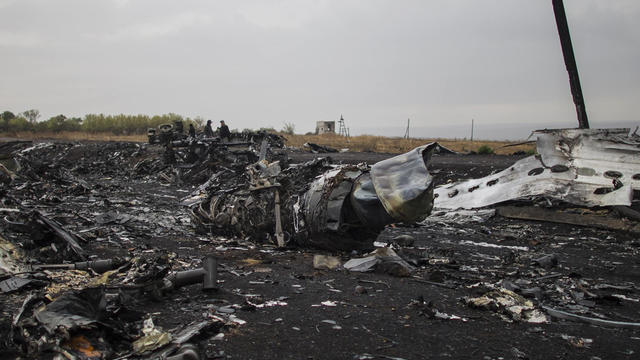 People stand near the remains of fuselage where the downed Malaysia Airlines flight MH17 crashed, near the village of Grabovo, in Donetsk region