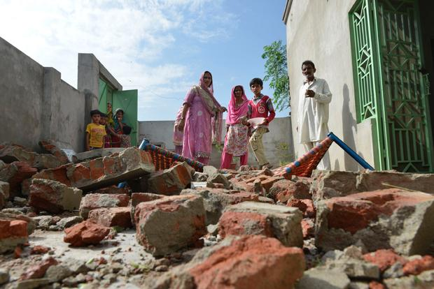 Civilians gaze at remains of home destroyed by India-Pakistan border dispute