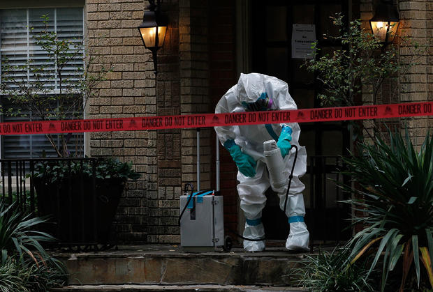 A man dressed in protective hazmat clothing treats the front porch of an apartment where a second person diagnosed with the Ebola virus resides