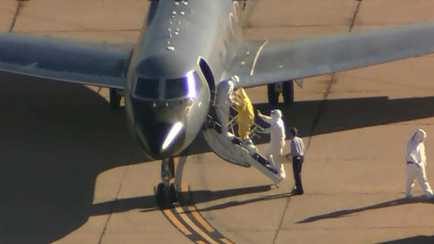 Ebola patient, Amber Vinson, seen in yellow suit, is boarding plane that will take her from Dallas to Emory University Hospital in Atlanta