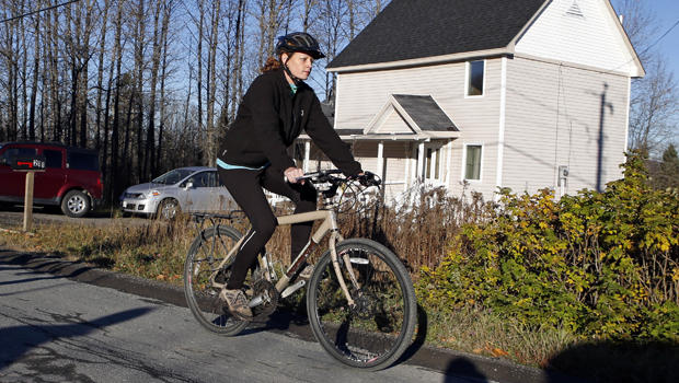 Nurse Kaci Hickox rides away from the home she is staying in on a rural road in Fort Kent, Maine, to take a bike ride Oct. 30, 2014.