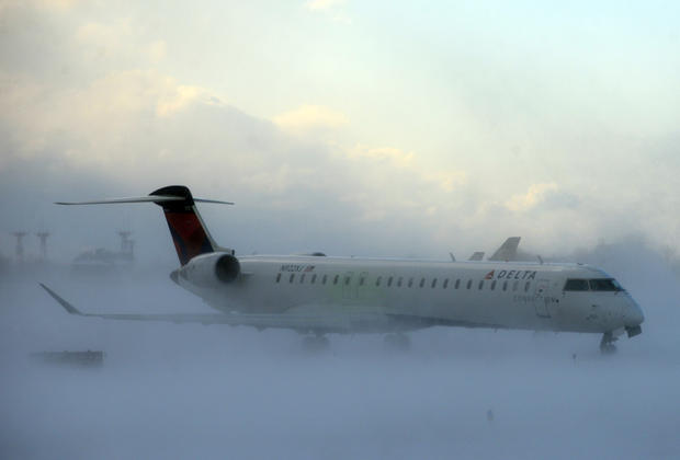 A lake-effect snowstorm with freezing temperatures affected travel, like this plane that negotiated its way through the snow at Buffalo Greater International Airport, in Buffalo, N.Y., Nov. 18, 2014.