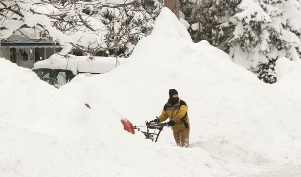 A man clears his driveway of snow following an autumn snowstorm in Buffalo, N.Y., Nov. 20, 2014.