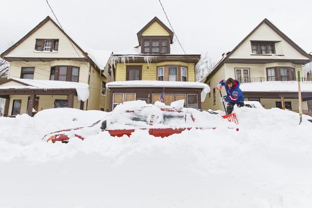 Lori Weishaar shovels snow from around her vehicle following an autumn snowstorm in Buffalo, N.Y., Nov. 20, 2014.