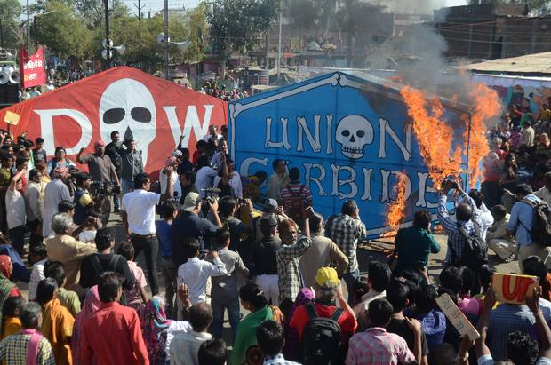 Indian residents and Bhopal gas disaster survivors set alight a Union Carbide banner as they commemorate the 30th anniversary of the disaster in Bhopal Dec. 3, 2014.