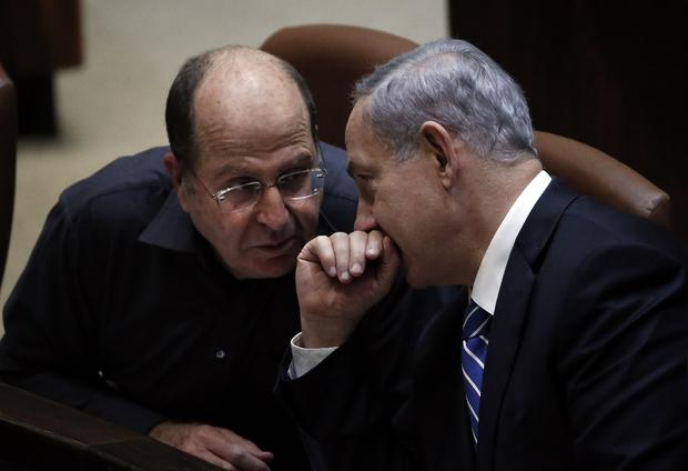 Israeli Prime Minister Benjamin Netanyahu (R) discusses with Israeli Defense minister Moshe Yaalon before the ultimate vote to dissolve the Israeli Parliament at the Knesset in Jerusalem