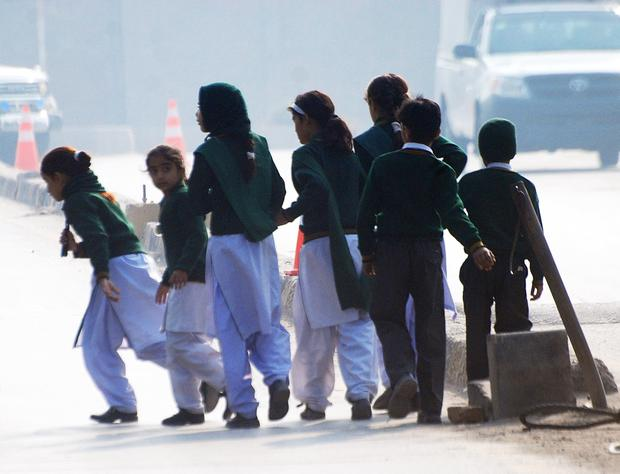 Schoolchildren cross a road as they move away from a military run school under attack by Taliban gunmen in Peshawar