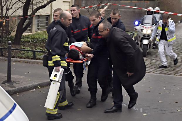 A victim is evacuated on a stretcher, Jan. 7, 2015, after armed gunmen stormed the offices of the French satirical newspaper Charlie Hebdo