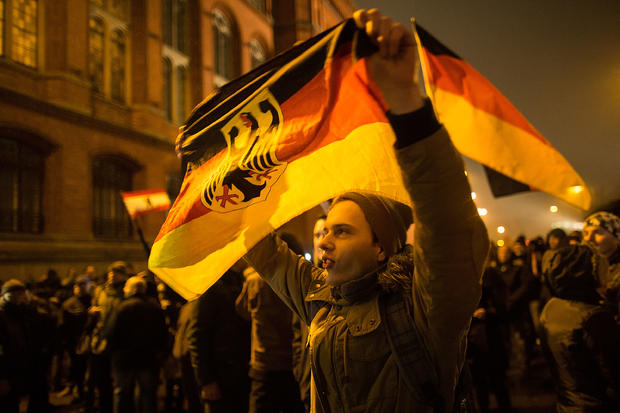 "A supporter of the PEGIDA movement holds a flag while supporters gather for a march in their first Berlin demonstration, which they have dubbed ""Baergida,"""