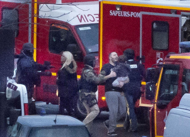A security officer directs released hostages after police stormed a kosher market to end a hostage situation in Paris Jan. 9, 2015.