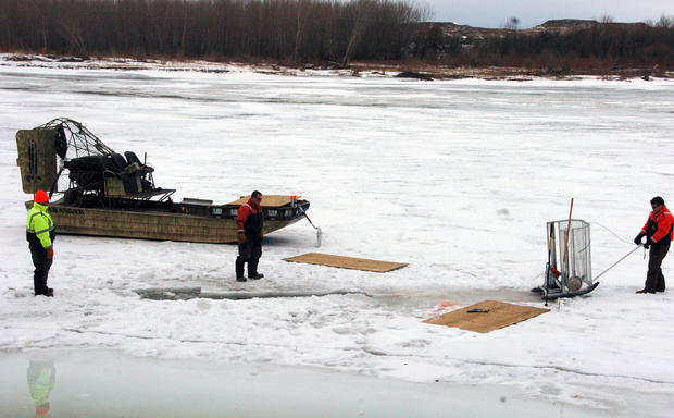 Cleanup workers cut holes into ice on Yellowstone River near Crane, Montana on January 19, 2015 as part of efforts to recover oil from upstream pipeline spill that released up to 50,000 gallons of crude oil