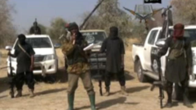 ​Boko Haram militants, and at center, the man claiming to be the group's leader, Abubakar Shekau, appear in a propaganda video
