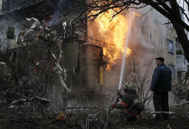 A firefighter works to extinguish a fire at a residential block, which was damaged by a recent shelling according to locals, on the outskirts of Donetsk, eastern Ukraine, Feb. 9, 2015.