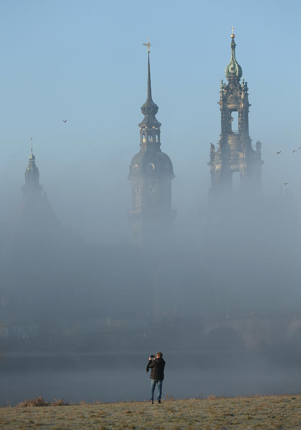 A man photographs fog rising from the Elbe River shrouding landmarks in the city center, including towers of the Residenzschloss Dresden palace, center, and the Catholic Hofkirche church, in Dresden, Germany, Feb. 12, 2015.