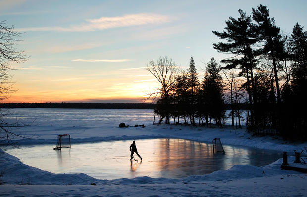 A youth plays pond hockey as the sun rises on Pigeon Lake in the region of Kawartha Lakes, Ontario, Feb. 4, 2015.