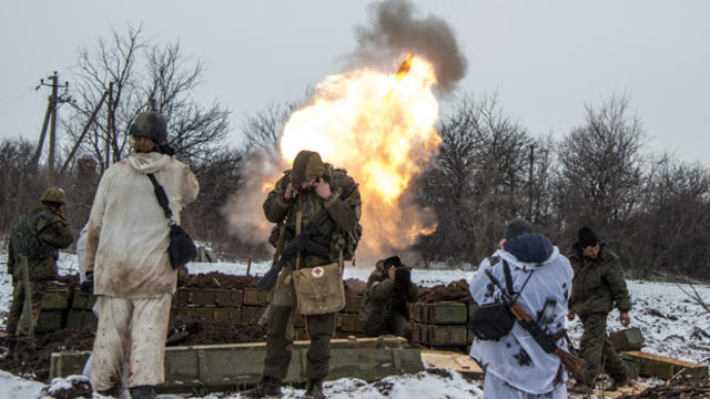 Russian-backed separatists cover their ears as they fire a mortar toward Ukrainian troops outside the village of Sanzharivka, northeast of Debaltseve, eastern Ukraine, Feb. 11, 2015.