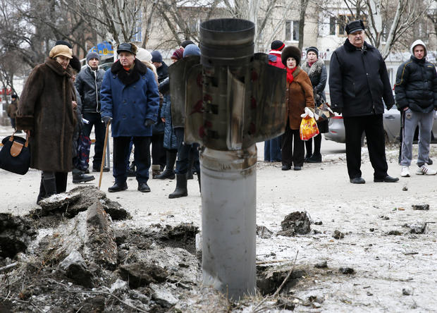 People look at the remains of a rocket shell on a street in the town of Kramatorsk, eastern Ukraine, Feb. 10, 2015.