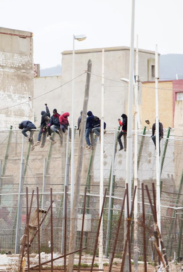 Would-be immigrants sit atop a border fence after attempting to cross from Morocco to the Spanish enclave of Melilla Feb. 10, 2015.