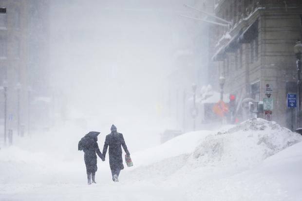 Couple walks hand-in-hand through snow in the Back Bay during a winter blizzard in Boston on February 15, 2015