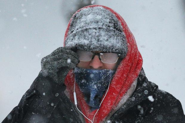 Pedestrian with his glasses fogged over walks through snow during winter blizzard in Cambridge, Massachusetts on February 15, 2015