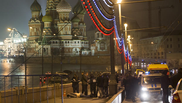 Russian police stand near the body of Boris Nemtsov, a former Russian deputy prime minister and opposition leader, near Red Square with St. Basil Cathedral in the background in Moscow