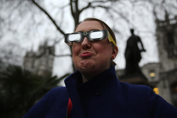 A woman shows her disappointment while wearing protective glasses as she tries, unsuccessfully, to get a glimpse of the partial solar eclipse