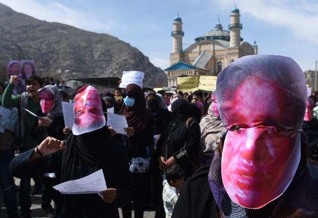 Afghan members of the Solidarity Party of Afghanistan wear masks bearing an impression of the bloodied face of Farkhunda, a woman who was lynched, during a protest against the attack in Kabul