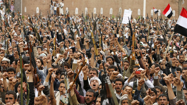 Shi'ite Muslim rebels hold up their weapons during a rally against airstrikes in Sanaa, Yemen, March 26, 2015.
