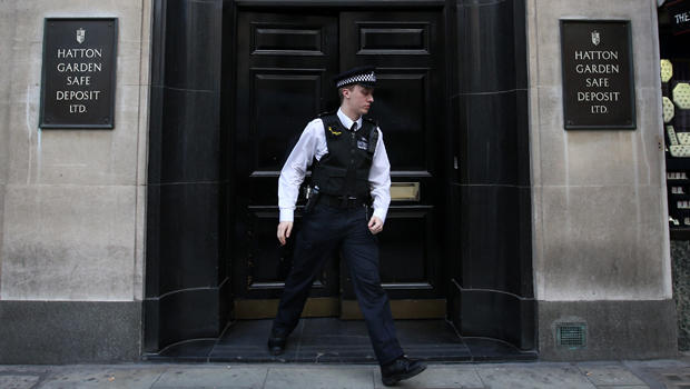 A police officer emerges from a Hatton Garden safe deposit center April 7, 2015, in London, England.