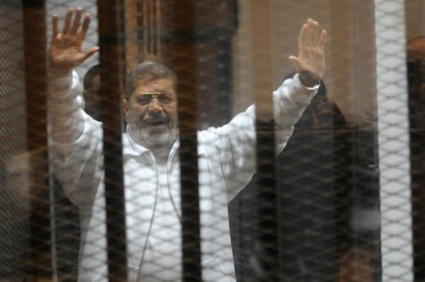 Egypt's deposed president Mohamed Morsi waves from inside the defendants cage during his trial