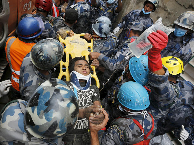 Earthquake survivor Pemba Tamang, 15, is rescued by the Armed Police Force from the collapsed Hilton Hotel