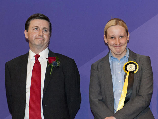 Newly elected Scottish National Party (SNP) member of parliament, Mhairi Black (R), next to the man she ousted, Labour candidate Douglas Alexander