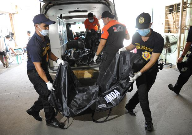 A police forensics team unloads a body bag containing the remains of a victim killed in a fire that gutted a footwear factory in Valenzuela city in suburban Manila