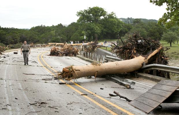 Department of Public Safety Trooper Marcus Gonzales walks on Highway 12 bridge over Blanco River, which was blocked by large trees after flooding in Wimberly, Texas, on May 24, 2015