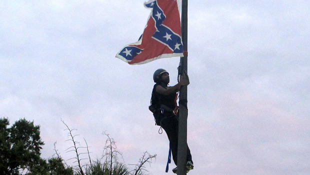 Bree Newsome of Charlotte, N.C., climbs a flagpole to remove the Confederate battle flag at a Confederate monument in front of the Statehouse in Columbia, S.C., June 27, 2015.