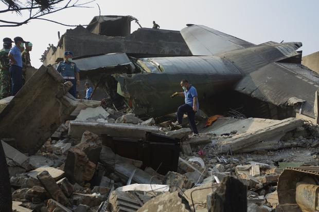 Military personnel and search and rescue teams comb through the wreckage of a military transport plane which crashed into a building
