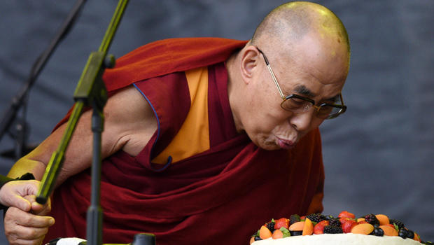 The Dalai Lama blows out a candle on a cake to celebrate his 80th birthday on the Pyramid stage as he visits the Glastonbury Festival of Music and Performing Arts on Worthy Farm near the village of Pilton in Somerset, England, June 28, 2015.