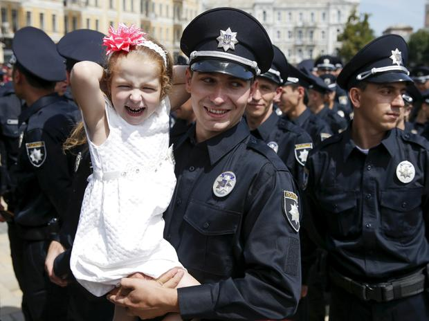 A police officer holds his daughter after an oath-taking ceremony, which started up the work of a new police patrol service, part of the Interior Ministry reform initiated by Ukrainian authorities, in Kiev, Ukraine