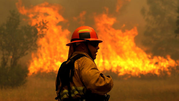 A firefighter monitors flames from the Rocky Fire as it approaches a home on July 31, 2015, in Lower Lake, California.