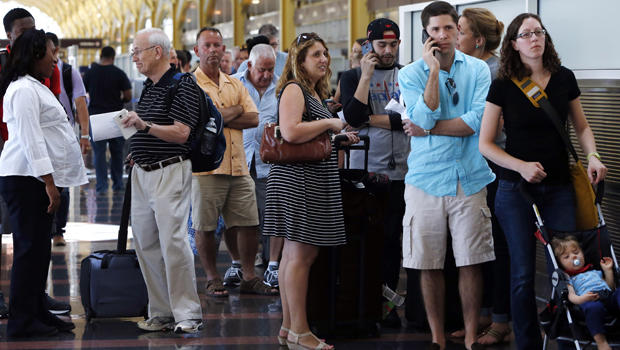 People stand in line at Washington's Reagan National Airport after technical issues at a Federal Aviation Administration center in Virginia caused delays Aug. 15, 2015.