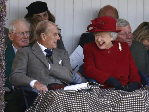 Britain's Queen Elizabeth and her husband Prince Philip watch the sack race at the annual Braemar Highland Gathering in Braemar, Scotland, Sept. 5, 2015.