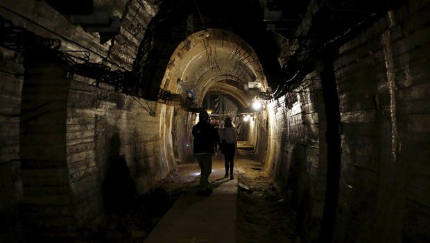 "People walk through a tunnel, which is part of the Nazi Germany ""Riese"" construction project, under the Ksiaz castle in an area where a Nazi train is believed to be, in Walbrzych, Poland, Sept. 3, 2015."